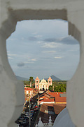 Exterior of the El Calvario Church seen through an white arch from the Leon Cathedral, Leon, Nicaragua