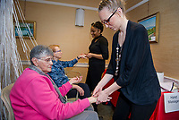 """Peg Petrie and Blanche Sleeper receive hand massages and wax treatment from Caitlin McAfee and Seanya Wilson from Empire Beauty School during the Taylor Home's """"Spa Day"""" at the Woodside Building for their Valentine's Day activity on Wednesday.  (Karen Bobotas/for the Laconia Daily Sun)"""