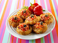 Mini rosti topped with cheese and salsa in a party stting