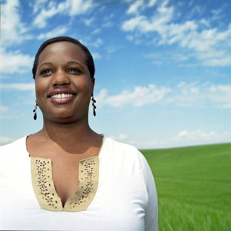 Young woman, 20 something, African-American heritage standing in wheat field smiling.