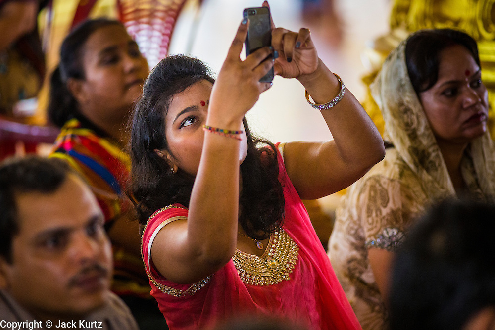 """15 SEPTEMBER 2013 - BANGKOK, THAILAND: A Hindu woman photographs services with her iPhone on the last day of Ganesha Chaturthi celebrations at Shiva Temple in Bangkok. Ganesha Chaturthi is the Hindu festival celebrated on the day of the re-birth of Lord Ganesha, the son of Shiva and Parvati. The festival, also known as Ganeshotsav (""""Festival of Ganesha"""") is observed in the Hindu calendar month of Bhaadrapada. The festival lasts for 10 days, ending on Anant Chaturdashi. Ganesha is a widely worshipped Hindu deity and is revered by many Thai Buddhists. Ganesha is widely revered as the remover of obstacles, the patron of arts and sciences and the deva of intellect and wisdom. The last day of the festival is marked by the immersion of the deity, which symbolizes the cycle of creation and dissolution in nature. In Bangkok, the deity (statue) was submerged in the Chao Phraya River.     PHOTO BY JACK KURTZ"""