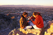 Two female hikers enjoy sunrise over Valley of the Sun from Squaw Peak, Phoenix, Arizona..Subject photograph(s) are copyright Edward McCain. All rights are reserved except those specifically granted by Edward McCain in writing prior to publication...McCain Photography.211 S 4th Avenue.Tucson, AZ 85701-2103.(520) 623-1998.mobile: (520) 990-0999.fax: (520) 623-1190.http://www.mccainphoto.com.edward@mccainphoto.com.
