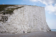Tourists on Cuckmere Haven beach stand very close to the cliff edge of Seven Sisters Cliffs on the 25th of August 2021 near Seaford, East Sussex, United Kingdom. The Seven Sisters are a series of chalk cliffs by the English Channel. They form part of the South Downs in East Sussex, between the towns of Seaford and Eastbourne in southern England. Cliff falls are common along these cliffs as they are formed from chalk.