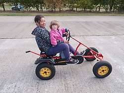 Girl giving toddler a ride on a pedal-operated go-cart