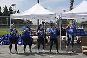 Volunteers greet motorists at the Dodger Day Drive-Thru at Belvedere Park, Tuesday, June 30, 2020, in Los Angeles. The event was hosted by The Los Angeles Dodgers Foundation, which distributed food boxes, books, sports equipment, clothing, toys and hygiene supplies to more than 1,000 registered youth from the Boyle Heights, East Los Angeles, La Puente and Monterey Park communities.