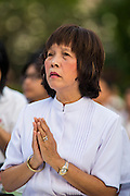 20 OCTOBER 2012 - BANGKOK, THAILAND: A woman prays for peace in southern Thailand during a special alms giving ceremony in Bangkok. More than 2,600 Buddhist Monks from across Bangkok and thousands of devout Thai Buddhists attended the mass alms giving ceremony in Benjasiri Park in Bangkok Saturday morning. The ceremony was to raise food and cash donations for Buddhist temples in Thailand's violence plagued southern provinces. Because of an ongoing long running insurgency by Muslim separatists many Buddhist monks in Pattani, Narathiwat and Yala, Thailand's three Muslim majority provinces, can't leave their temples without military escorts. Monks have been targeted by Muslim extremists because, in the view of the extremists, they represent the Thai state.    PHOTO BY JACK KURTZ