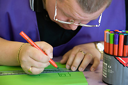 Day Service user with learning disability using coloured felt tip pen and ruler to draw,