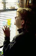 Woman age 54 peering through window in silhouette.  St Paul  Minnesota USA