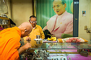 25 JUNE 2013 - BANGKOK, THAILAND:     A Buddhist monk looks at amulets under a portrait Bhumibol Adulyadej, the King of Thailand, in the Amulet Market in Bangkok. The market is adjacent to Wat Mahathat, between Maharat Road and the Chao Phraya River.    PHOTO BY JACK KURTZ