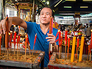 """26 AUGUST 2013 - BANGKOK, THAILAND: A man lights candles and pray at the Poh Teck Tung Foundation for Hungry Ghost Month in Bangkok. Poh Teck Tung operates hospitals and schools and provides assistance to the poor in Thailand. The seventh lunar month (August - September in 2013) is when the Chinese community believes that hell's gate will open to allow spirits to roam freely in the human world for a month. Many households and temples will hold prayer ceremonies throughout the month-long Hungry Ghost Festival (Phor Thor) to appease the spirits. During the festival, believers will also worship the Tai Su Yeah (King of Hades) in the form of paper effigies which will be """"sent back"""" to hell after the effigies are burnt.    PHOTO BY JACK KURTZ"""