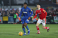 AFC Wimbledon defender Paul Kalambayi (30) taking on Barnsley attacker Kieffer Moore (19) during the EFL Sky Bet League 1 match between AFC Wimbledon and Barnsley at the Cherry Red Records Stadium, Kingston, England on 19 January 2019.