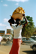 A woman carries bananas in Kampala city, Uganda