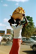 A woman carries bananas in Kampala city, Uganda