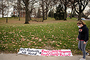 """20 NOVEMBER 2020 - DES MOINES, IOWA: A woman walks past a banner on the lawn of the Iowa Governor's Mansion. About 20 people participated in a protest in front of the Iowa Governor's Mansion Friday. They called on Governor Kim Reynolds to immediately issue a comprehensive mask mandate across Iowa. Reynolds, a Republican, has ordered a partial mask mandate that excuses some congregate settings, like classrooms. Iowa has one of the highest per capita COVID-19 infection rates in the country and is dealing with wide """"community spread"""" of the Coronavirus (SARS-CoV-2) throughout the state.        PHOTO BY JACK KURTZ"""
