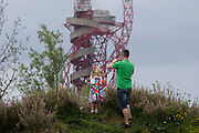 Families climb on to a small hill that has the Orbit artwork tower in the background. during the London 2012 Olympics. Standing 115 metres high, the Orbit is the tallest art structure in Britain – offering views over the Olympic Stadium, Olympic Park and the whole of London. This land was transformed to become a 2.5 Sq Km sporting complex, once industrial businesses and now the venue of eight venues including the main arena, Aquatics Centre and Velodrome plus the athletes' Olympic Village. After the Olympics, the park is to be known as Queen Elizabeth Olympic Park.