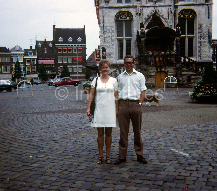 Portrait of a young couple while on holiday in Gouda, the Netherlands in the 1970s. Standing on the street's cobbles, the married couple smile in the Dutch city in front of the 15th century Gothic City Hall. Gouda population 70,828 in 2009) is a city and municipality in the western Netherlands, in the province of South Holland. Gouda, which was granted city rights in 1272, is famous for its Gouda cheese, smoking pipes, and 15th-century city hall.