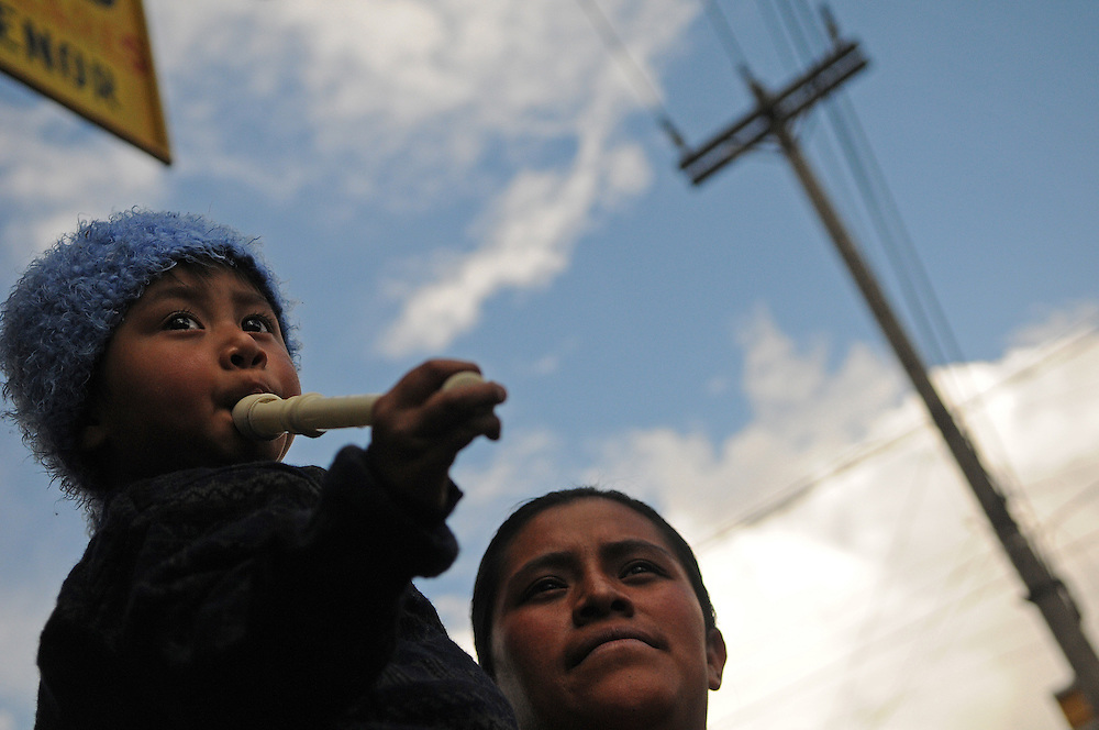 A young boy and his mother watch the Jesus of Nazareth Procession  in Quetzaltenago Guatemala Sunday afternoon.