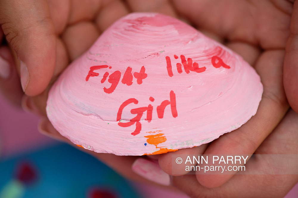 Merrick, New York, U.S. August 15, 2020. ANNIE FITZPATRICK, 12-years-old, and friends hold a pink shell with Fight like a Girl written on it.  Lizzie's Army painted shells to sell to raise funds to donate to American Cancer Society Making Strides Against Breast Cancer. Annie's 24 year old sister Lizzie was diagnosed with Triple Negative Breast Cancer in late June . Over $3,000 has been raised so far through shell sales and GoFundMe.