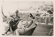Never-before-seen photos of John F. Kennedy and wife Jackie vacationing with friends in Cape Cod set to go up for auction<br /> <br /> A set of rare photographs which show former US President John F. Kennedy and his wife Jackie relaxing on vacation in Cape Cod will go up for auction later this month.<br /> The candid images were taken by Washington Post heiress Katharine Graham at Listerine heiress Rachel 'Bunny' Mellon's Cape Cod beach shack in August 1961, just two years before JFK's assassination and show the couple enjoying a laid-back holiday in the company of some of their closest friends and family, including Mrs Mellon and her banker husband Paul.<br /> In one series of photos, JFK can be seen eating a relaxed meal outside on the deck, while deep in conversation with his host Mrs Mellon. His wife is pictured just a few meters away, seated alongside Mr Mellon.<br /> Another set of images, which will be auctioned off by RR Auction House on February 19, shows the then-44-year-old former President enjoying a swim in the bay alongside a male companion, before climbing up out of the water and onto what appears to be a dock, while reaching for a towel.<br /> None of the images seem to show JFK wearing his back brace, which was designed to help alleviate his chronic back pain - and which he is believed to have been wearing on the day of his death.<br /> Meanwhile, a usually-immaculate Jackie can be seen looking carefree and relaxed, wearing a casual collection of beachwear - a far cry from the high-end fashions she was usually pictured in.<br /> One image shows her enjoying a cigarette, while deep in discussion with a male friend. <br /> In October last year, a set of 13 wedding negatives from the Kennedys' spectacular wedding ceremony and celebration fetched $34,000 at auction, while in 2013, a Polaroid picture depicting the exact moment in which JFK was shot went under the hammer in Cincinnati.<br /> Surprisingly, the image, which was predicted to sell for up to $