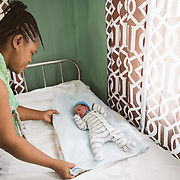 INDIVIDUAL(S) PHOTOGRAPHED: Fernande Delice (left) and Emmanuelo Wariens (right). LOCATION: St. Damien Hospital, Nos Petits Frères et Sœurs, Tabarre 41 Commune, Haïti. CAPTION: Fernande Delice adjusts her tiny newborn son's blankets in the maternity ward at St. Damien Hospital.
