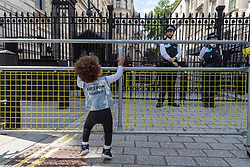 © Licensed to London News Pictures. 31/07/2021. London, UK. A toddler child climbs the security gate outside Downing Street taking part in a protest with families demonstrationing in support of children rights against Covid vaccination and regulations. Photo credit: Ray Tang/LNP