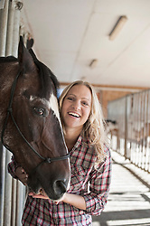 Portrait of a mid adult woman with her horse in barn and smiling, Bavaria, Germany