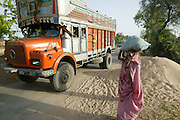 IND.MWdrv04.152.x..MIshri Yadav, 35, waits for a truck to pass before crossing the road to her home village after harvesting wheat. Her family grows one planting of wheat and then rice during the rest of the year. Mishri's family must pay half of the harvest to the owner of the land that they farm. Ahraura Village, Uttar Pradesh, India. Revisit with the family, 2004. The Yadavs were India's participants in Material World: A Global Family Portrait, 1994 (pages: 64-65), for which they took all of their possessions out of their house for a family-and-possessions-portrait. Work..