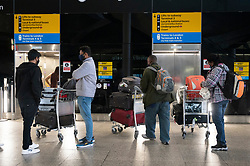 © Licensed to London News Pictures. 19/01/2021. London, UK. Travellers in the international arrival area of Heathrow Airport near London. Travel corridors in the the UK were closed at 04:00 hours on 18 January 2021 as British government declared. Travellers arriving to England from anywhere outside the UK have to to self-isolate for 10 days and must have proof of a negative coronavirus test. Photo credit: Ray Tang/LNP