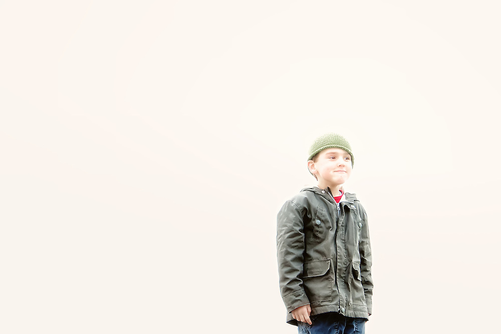 Portrait of boy wearing a green toque with matching jacket.