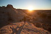 Leif Anderson hikes at sunrise through the sandstone formations of the San Rafael Swell, Utah.