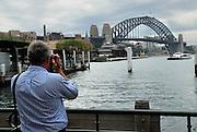 Man photographing Sydney Harbour Bridge. Circular Quay, Sydney, Australia