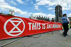 © Licensed to London News Pictures. 01/09/2020. LONDON, UK.  Activists from Extinction Rebellion unfurl a banner at a climate change protest in Parliament Square on the day that Members of Parliament return to Westminster after the summer recess.  Photo credit: Stephen Chung/LNP