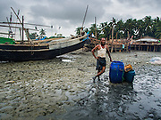 07 NOVEMBER 2014 - SITTWE, RAKHINE, MYANMAR: A Rohingya man who works building boats stands in the port of an IDP camp for Rohingya Muslims near Sittwe. The government of Myanmar has forced more than 140,000 Rohingya Muslims who used to live in Sittwe, Myanmar, into squalid Internal Displaced Person (IDP) camps. The forced relocation took place in 2012 after sectarian violence devastated Rohingya communities in Sittwe and left hundreds dead. None of the camps have electricity and some have been denied access to regular rations for nine months. Conditions for the Rohingya in the camps have fueled an exodus of Rohingya refugees to Malaysia and Thailand. Tens of thousands have put to sea in rickety boats hoping to land in Malaysia but sometimes landing in Thailand. The exodus has fueled the boat building boom on the waterfront near the camps. Authorities expect the pace of refugees fleeing Myanmar to accelerate during the cool season, December through February, when there are fewer storms in the Andaman Sea and Bay of Bengal.   PHOTO BY JACK KURTZ