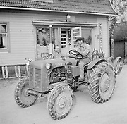 Farmer on tractor talking to man village shop store Finland 1955