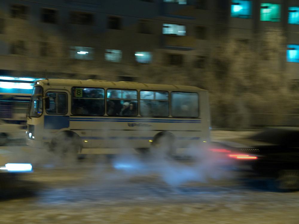Abendlicher Verkehr in der Innenstadt von Jakutsk. Jakutsk wurde 1632 gegruendet und feierte 2007 sein 375 jaehriges Bestehen. Jakutsk ist im Winter eine der kaeltesten Grossstaedte weltweit mit durchschnittlichen Winter Temperaturen von -40.9 Grad Celsius. Die Stadt ist nicht weit entfernt von Oimjakon, dem Kaeltepol der bewohnten Gebiete der Erde.<br /> <br /> Evening traffic in the city center of Yakutsk. Yakutsk was founded in 1632 and celebrated 2007 the 375th anniversary - billboard announcing the celebration. Yakutsk is a city in the Russian Far East, located about 4 degrees (450 km) below the Arctic Circle. It is the capital of the Sakha (Yakutia) Republic (formerly the Yakut Autonomous Soviet Socialist Republic), Russia and a major port on the Lena River. Yakutsk is one of the coldest cities on earth, with winter temperatures averaging -40.9 degrees Celsius.