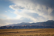 Wide angle of Great Sand Dunes National Park and the Sangre de Cristo Mountains with virga from a thunderstorm rising into the evening sky, San Luis Valley, Colorado.