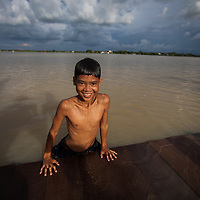 Boys play on the Cambodian side of the Mekong river, the other bank is Vietnam.