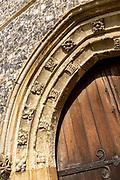 Historic village parish church at Kenton, Suffolk, England, UK stone doorway arch carved stonework detail casement mouldings
