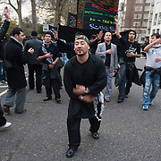LONDON, ENGLAND - DECEMBER 27:  Shiite worshippers beat on their chest during the Ashura procession in Central London on December 27, 2009 in London, England.Ashura is a 10 day period of mourning for Imam Hussein, the seven-century grandson of Prophet Mohammad who was killed in a battle in Karbala in Iraq, in 680 AD.  (Photo by Marco Secchi/Getty Images)