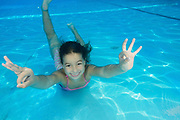 Young girl of 7 swimming underwater gives the OK hand gesture