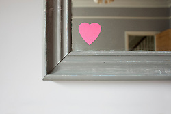 Heart shaped adhesive note on mirror (Credit Image: © Image Source/Ian Nolan/Image Source/ZUMAPRESS.com)