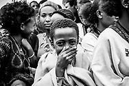 Lalibela, Ethiopia - August 23, 2010: At a large gathering of people at a religious/cultural festival in the historic town of Lalibela, best known for its centuries-old stone churches, a boy smiles and laughs while interacting with a photographer.