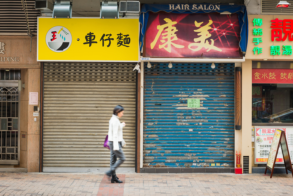 Motion blur of figure passing closed shops on street in Kowloon, Hong Kong