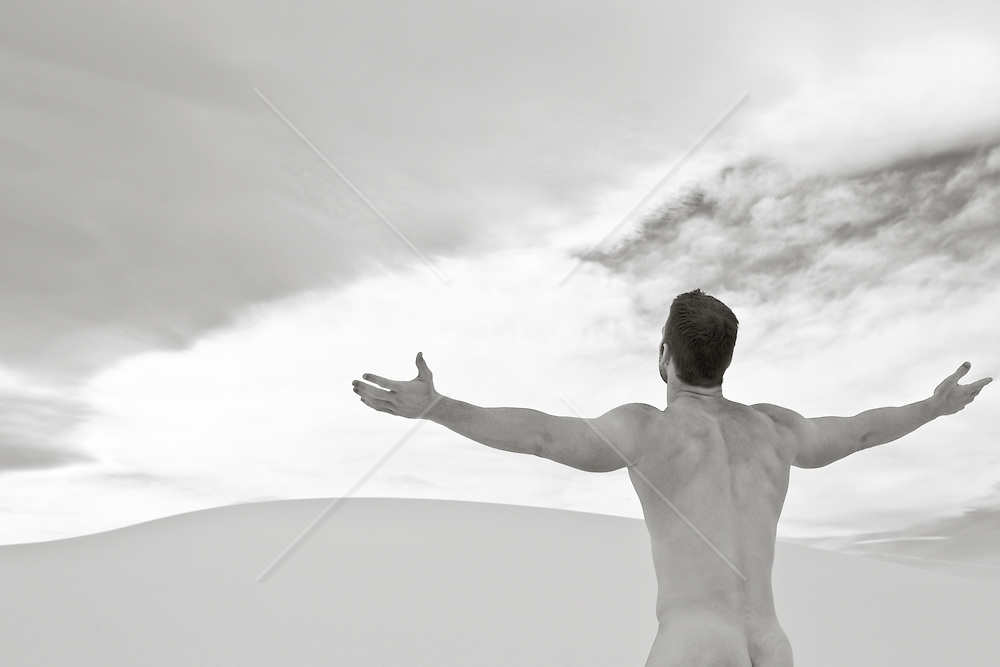 naked man with open arms facing a dramatic sky in the desert