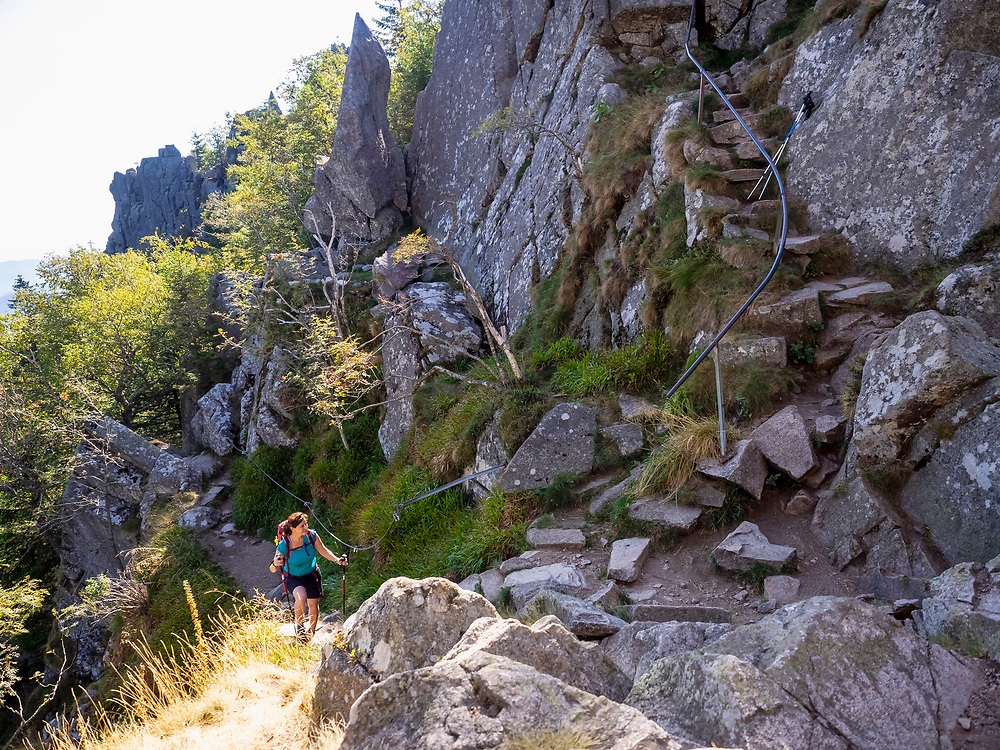 Women climbing up on narrow rocks in Vosges of Alsace at Lac Blanc, France
