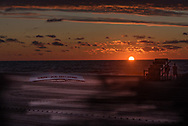 A blue and orange sky, streaks of light on the beach, a lifeboat and lifeguard chair on the beach at daybreak.