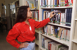 Teenage girl looking at books on library shelves,