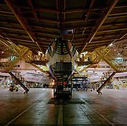 A Boeing 747 is surrounded by gantries during late night work by engineering staff perform maintenance checks in the British Airways engineering hangar on the far side of London's Heathrow airport. As a landscape of confusing lines and linear design, we see the paintwork of the jet aircraft echoed in those of the platform struts and the steps that help the maintenance crews gain height and access to the high places required for the work to be carried out. At its tallest point, the 747's tail is 63 feet (19m).
