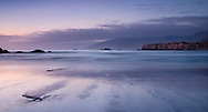 A wide view and long exposure captures soft ocean waves in the last light of the day at a remote Big Sur beach