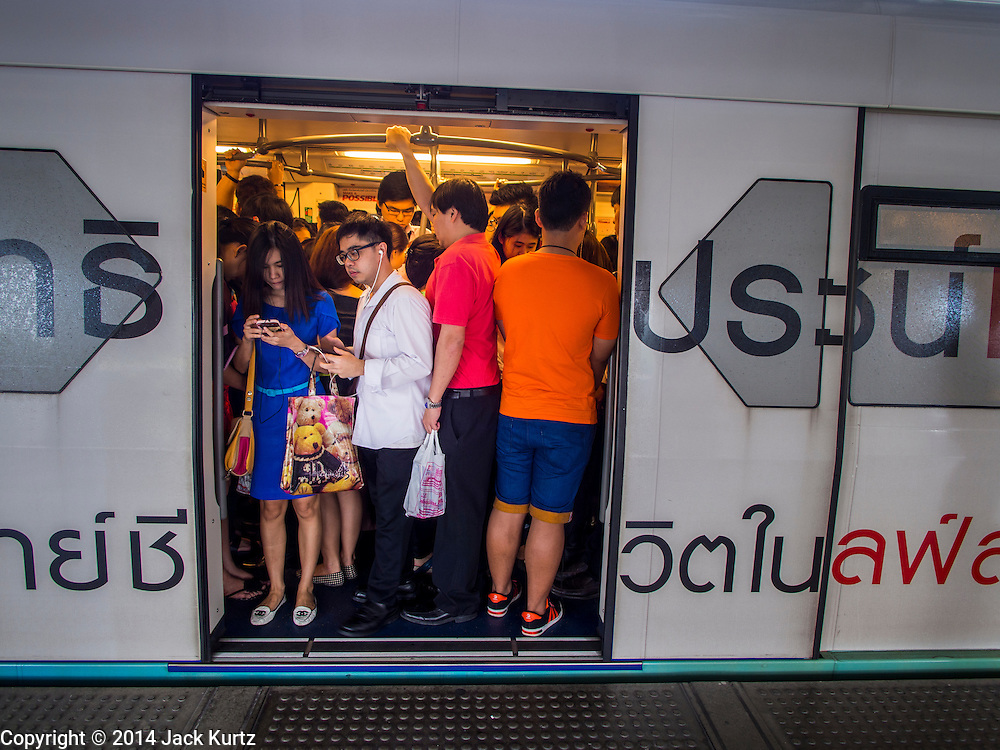 28 OCTOBER 2014 - BANGKOK, THAILAND: Passengers crowd into an inbound Bangkok Skytrain at the Saphan Taksin station. The Skytrain (called the BTS) system has a combined length of 36 kilometres and includes 34 stations, including Saphan Taksin. While there are two train tracks for most stretches of the Skytrain system, the portion on the Saphan Taksin Bridge spanning the Chao Phraya River has just one track due to limited space, causing a bottleneck when an outbound train and inbound train arrive at the bridge at the same time. The Bangkok Metropolitan Authority (BMA) had sought permission from the Department of Rural Roads to expand the Taksin Bridge in order to make way for an additional track, but the department had said it was not possible. The Saphan Taksin  station was originally supposed to be temporary and is one of the busiest on the system. It's a connecting station for the Chao Phraya River boats used by Thai commuters coming into the city from neighboring provinces and tourists who use the boats to go upriver into the old parts of Bangkok from the central business district. More than 4,000 commuters a day use the station. The BMA plans to build an elevated moving sidewalk to the river from Surasak BTS station about one kilometer away. Surasak is the nearest station to Saphan Taksin. The Skytrain system has a combined length of 36 kilometres and includes 34 stations, including Saphan Taksin.        PHOTO BY JACK KURTZ
